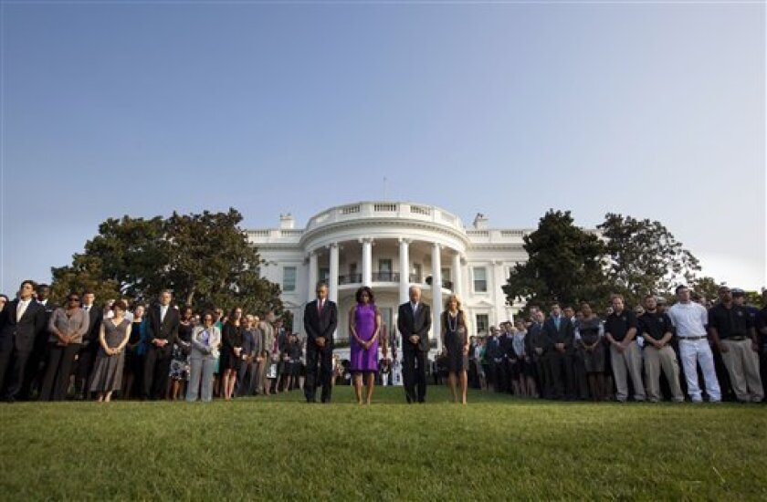 President Barack Obama, first lady Michelle Obama, Vice President Joe Biden and Jill Biden join members of the White House staff during a moment of silence to mark the 12th anniversary of the 9/11 attacks, Wednesday, Sept. 11, 2013, on the South Lawn of the White House in Washington. (AP Photo/Pablo Martinez Monsivais)