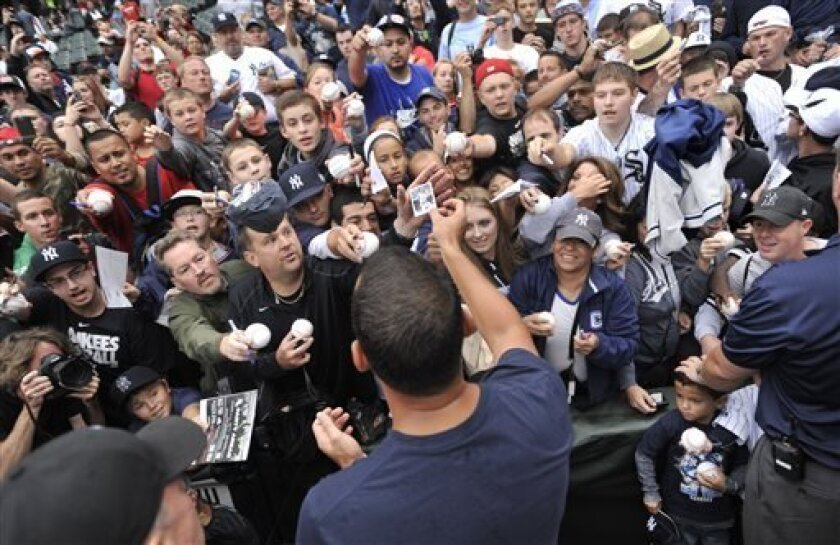 New York Yankees' Alex Rodriguez, bottom center, signs autographs at U.S. Cellular Field before a baseball game against the Chicago White Sox, Monday, Aug. 5, 2013, in Chicago. Rodriguez was suspended through 2014 and All-Stars Nelson Cruz, Jhonny Peralta and Everth Cabrera were banned 50 games apiece Monday when Major League Baseball disciplined 13 players in a drug case, the most sweeping punishment since the Black Sox scandal nearly a century ago. (AP Photo/Paul Beaty)