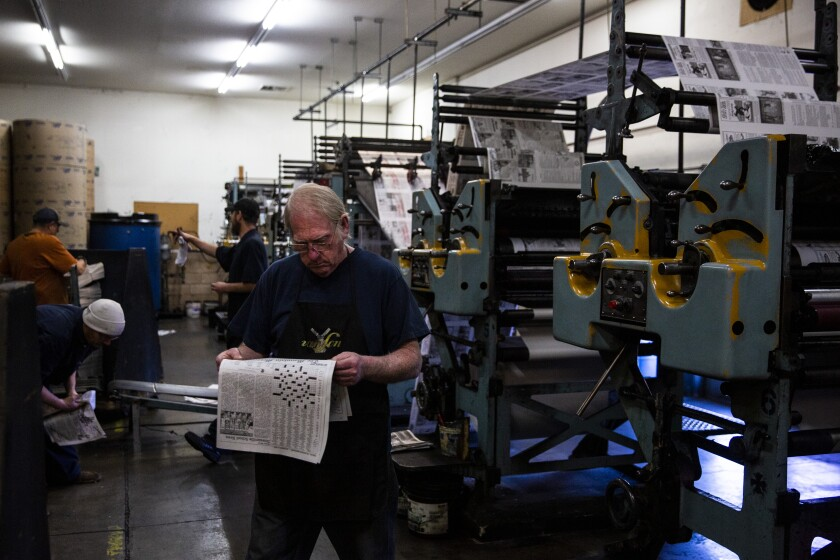 Press operators check the freshly printed issue of The Mountain Messenger, the oldest weekly newspaper in California.