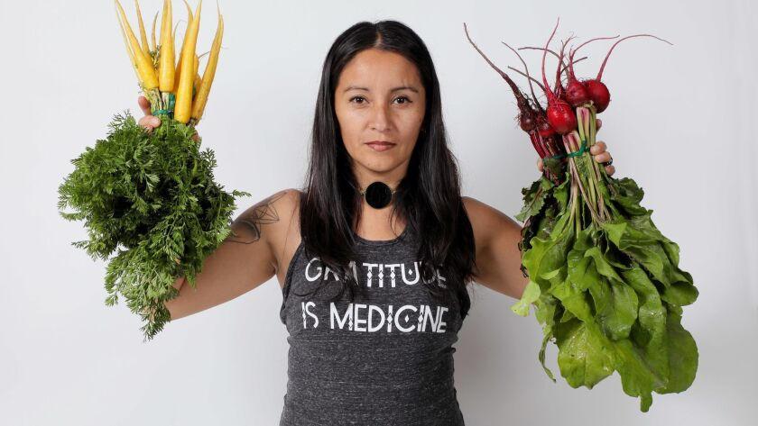 Portrait of Jessica Sanchez with organic vegetables grown at Terra Madre Gardens in Escondido where she is one the farmers and owners.
