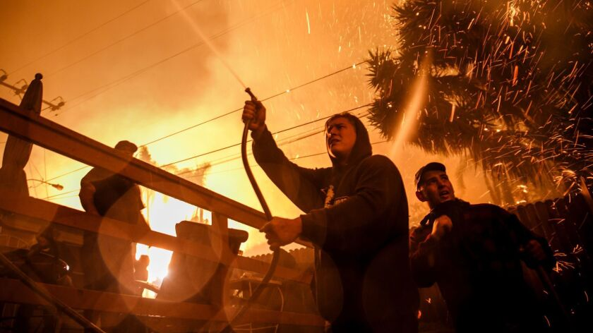 Embers fly around Brandon Baker, center, and Prescott McKenzie, right, during a 2017 wildfire in Ventura. New guidelines are intended to give residents more warning of approaching fires and extreme weather.