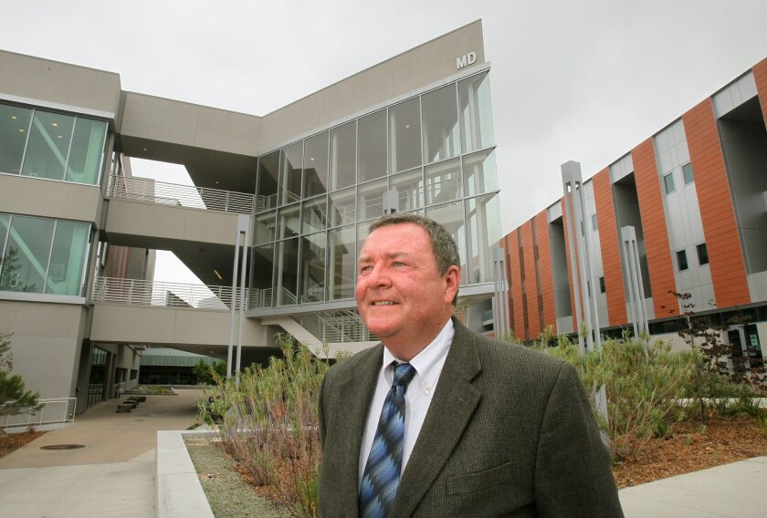 Portrait of Palomar College President Robert Deegan who is retiring soon after leading the community college for ten years. In the background are two of the college's newer buildings built while he was in charge. At left is the Multi-Disciplinary Building and at right is the Humanities Building.