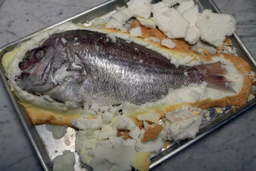 Slat-roasted fish is cooked, covered in salt.