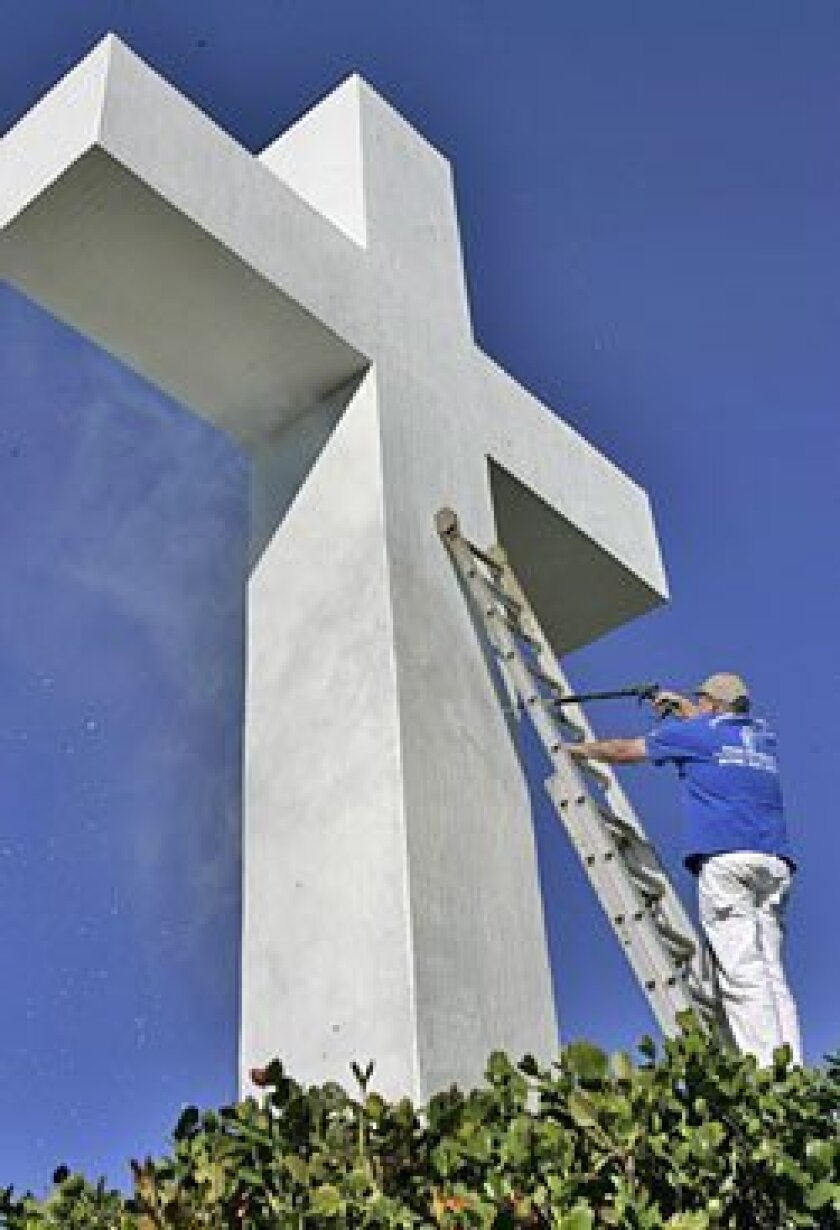 Mike Calabrese of Jackson Stone and Patio power-washed the 35-foot-tall cross. The fixture was also repainted. (Nancee E. Lewis / Union-Tribune)