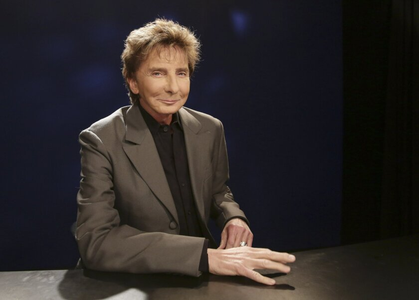 FILE - In this Oct. 27, 2014 file photo, singer-songwriter and producer Barry Manilow poses for a photograph during an interview in New York. Manilow has been forced to postpone two concerts following a rough week of oral surgery. Manilow had surgery twice earlier this week, and still managed to ma