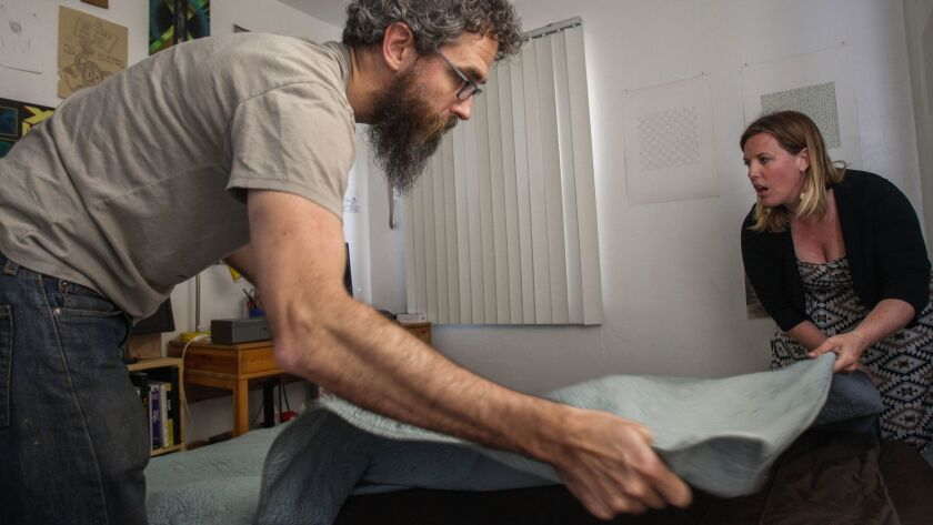 Blair Overstreet and her husband Matt Dunn spreads a blanket over an inflated mattress in their spare bedroom in hopes of being able to offer the room to a family that is part of the Central American caravan seeking asylum in the U.S.