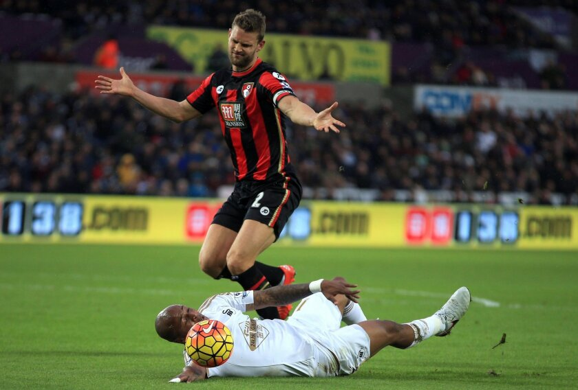 Swansea City's Andre Ayew hits the ground after challenge from AFC Bournemouth's Simon Francis , during the English Premier League soccer match between Swansea City and AFC Bournemouth, at the Liberty Stadium, in Swansea, Wales, Saturday Nov. 21, 2015. (Nick Potts/PA via AP) UNITED KINGDOM OUT