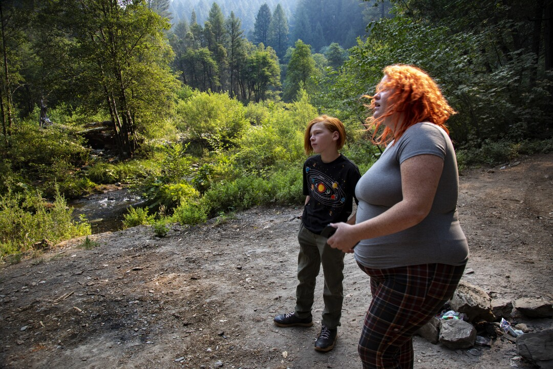 Kayla Wilson and son JJ stand at a wilderness campsite.