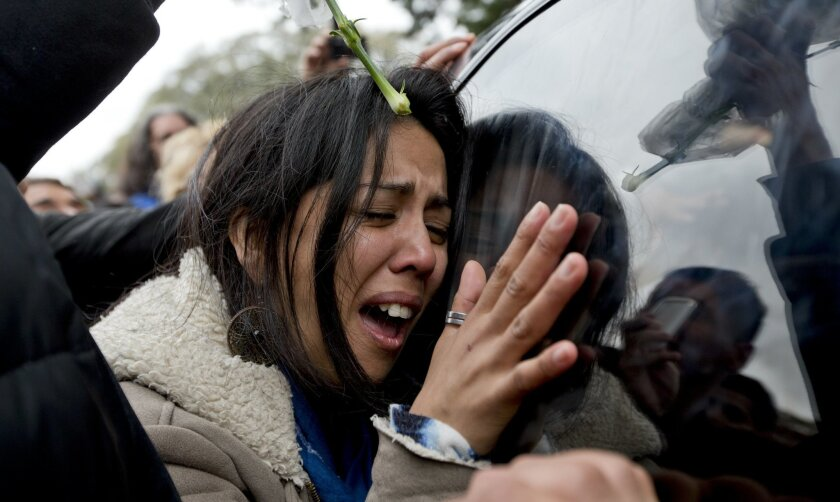 A woman weeps as she leans against the window of the funeral car transporting the remains of Argentine rock star Gustavo Cerati, in Buenos Aires, Argentina, Friday, Sept. 5, 2014. Cerati, the former frontman for Soda Stereo, died on Thursday, four years after a stroke put him in a coma and ended the career of one of Latin America's most influential musicians. (AP Photo/Natacha Pisarenko)