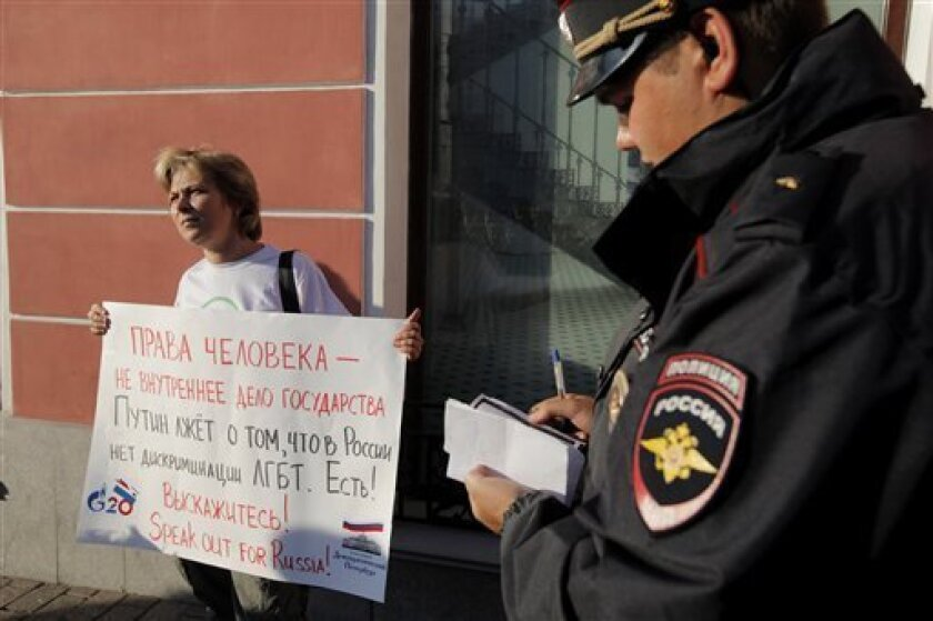 """In this Thursday, Sept. 5, 2013 photo, a Russian policeman checks ID of a gay rights activist holding a protest poster in downtown St. Petersburg, Russia. The poster reads """" Putin lies, saying that there is no gay discrimination in Russia."""" (AP Photo/Elena Ignatyeva)"""