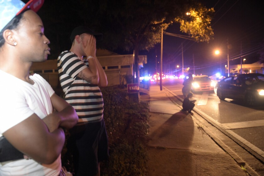 Jermaine Towns, left, and Brandon Shuford wait down the street from the Pulse nightclub in Orlando, Fla.