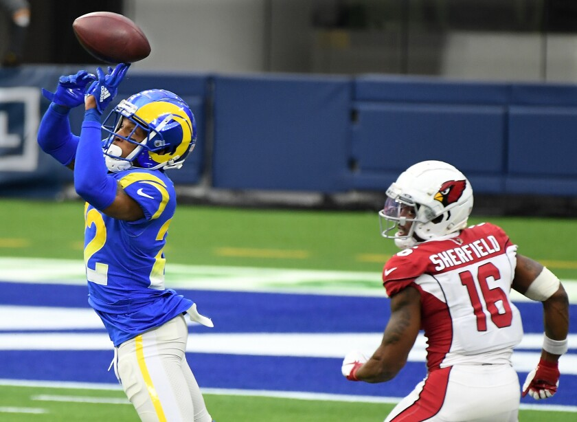 The Rams' Troy Hill intercepts a pass in front of the Cardinals' Trent Sherfield and turns the catch into a pick-six.