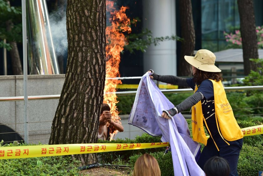 A woman rushes to extinguish the flames after an 81-year-old man set himself on fire in South Korea outside the Japanese embassy during a protest over Japan's wartime conduct.