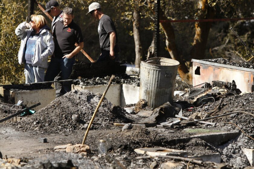 Cabin owner Candy Martin and her sons look through the charred debris of the mountain home where days earlier former cop Christopher Dorner died after a shootout with officers.