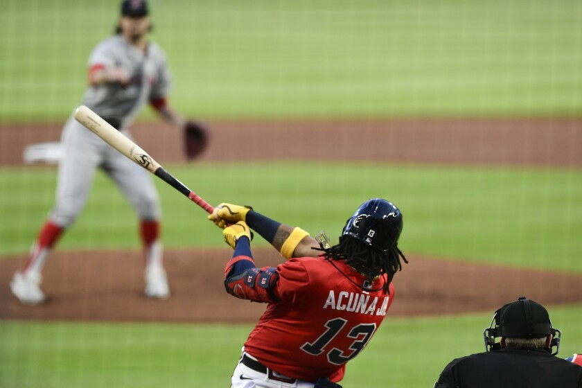 Atlanta Braves' Ronald Acuna Jr. (13) follows through on a home run to left field on a pitch by Boston Red Sox' Chris Mazza, top, during the first inning of a baseball game Friday, Sept. 25, 2020, in Atlanta. (AP Photo/John Amis)