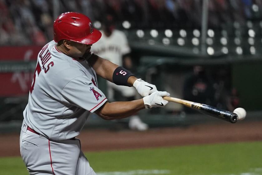 Angels' Albert Pujols hits a run-scoring single against the San Francisco Giants.