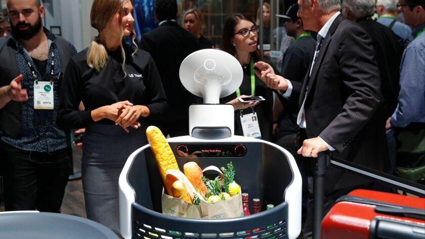 The Cloi shopping cart robot, center, appears on display at the LG booth during CES International, T