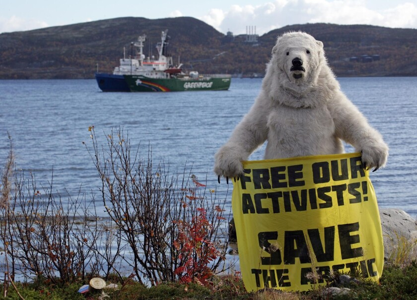 A Greenpeace activist dressed as a polar bear holds a banner in front of the group's seized ship, the Arctic Sunrise, which is moored next to a blue coast guard vessel in Russia's Kola Bay.
