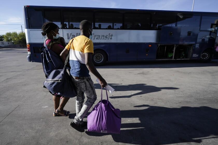 Haitian migrants carrying large bags walk toward a bus