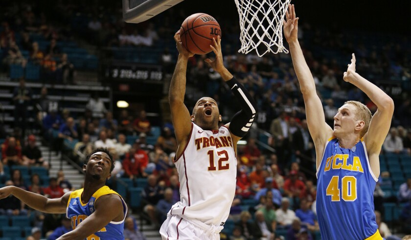 USC guard Julian Jacobs, center, shoots between UCLA guard Isaac Hamilton, left, and center Thomas Welsh during the first half of the first round of the Pac-12 men's tournament on Wednesday in Las Vegas.