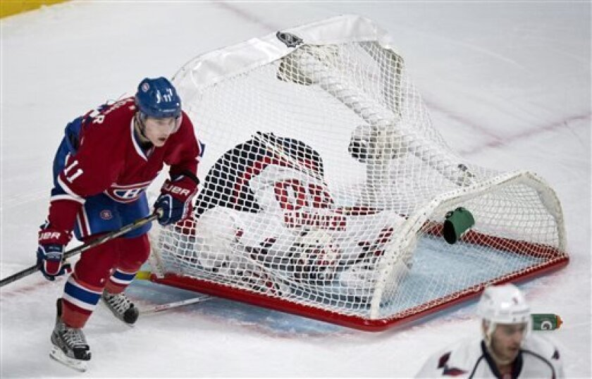 Washington Capitals goalie Michal Neuvirth gets caught underneath the fallen net as Montreal Canadiens' Brendan Gallagher skates by during first period NHL hockey action Tuesday, April 9, 2013 in Montreal. (AP Photo/The Canadian Press, Paul Chiasson)