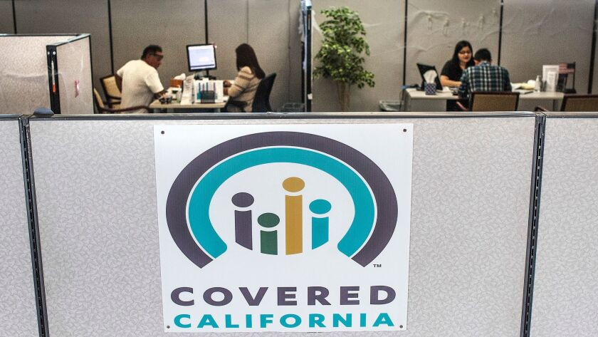Insurance agents help sign people up for insurance through the Covered California exchange at their