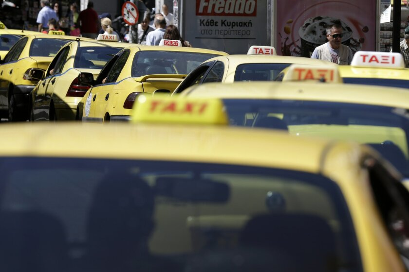 Taxi drivers wait for customers at Syntagma square in Athens, Monday, July 20, 2015. Taxi services and many goods become more expensive on Monday as a result of a rise in Value Added Tax approved by Parliament last week, among the first batch of austerity measures demanded by Greece's creditors. (AP Photo/Thanassis Stavrakis)