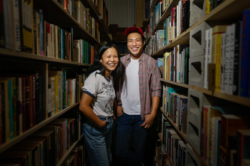Jenny Yang and Chris Capizzi, co-owners of A Good Used Book, stand in between bookshelves