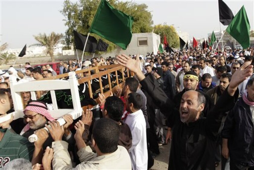 Bahrani anti-goverment carry the coffin of Ali Massour Khodier, 22, who died during clashes with riot police on early Thursday, during his funeral procession  in Sitra village, Bahrain, Friday, Feb. 18, 2011. (AP Photo/Hassan Ammar)