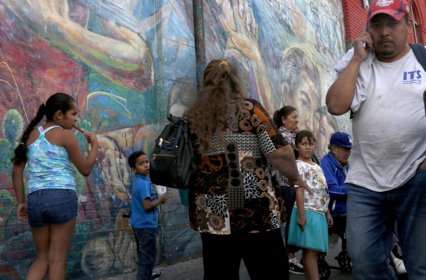 Latinos gather at a bus stop at the corner of Soto and Cesar Chavez in Boyle Heights.