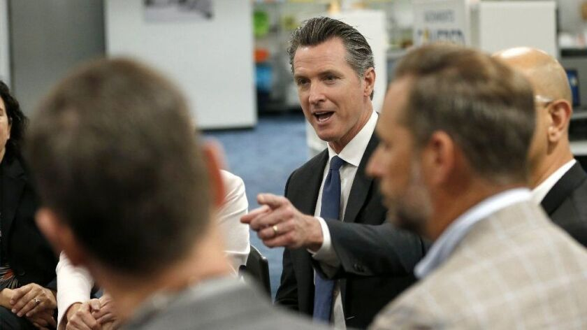 Gov. Gavin Newsom discusses his healthcare proposals at a round-table discussion with small-business owners on Tuesday in Sacramento.