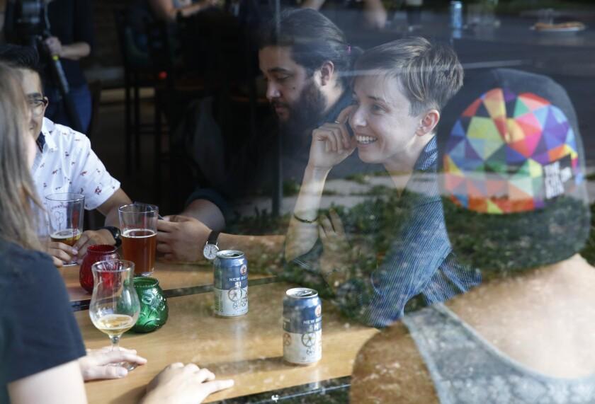 """Diana Downard, de 26 años y seguidora de Bernie Sanders que dice que votará a Hillary Clinton, toma unos tragos con amigos en un pub en Denver, el 6 de julio de 2016. """"Los millennials han sido descritos como apáticos, pero no lo son"""", dijo Downard. (AP Foto/Brennan Linsley)"""