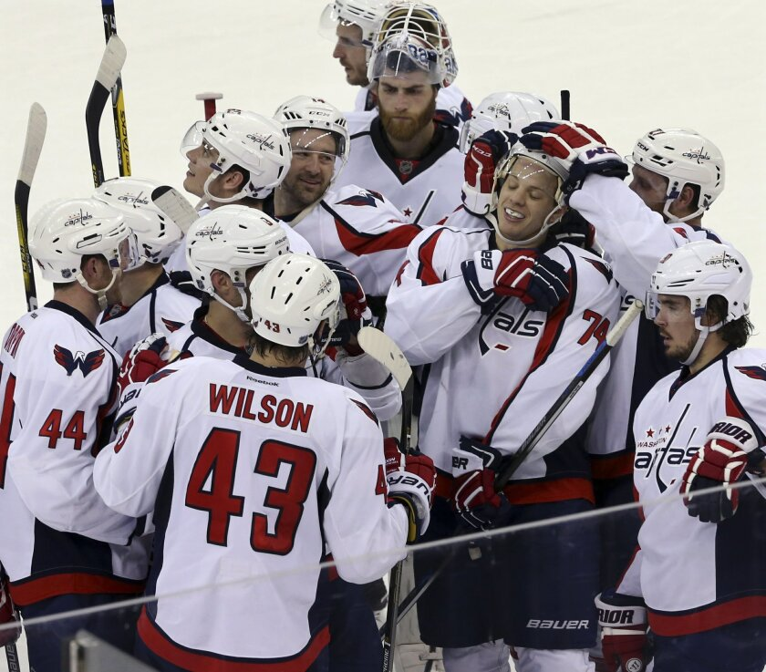 Washington Capitals players gather around defenseman John Carlson (74) as they celebrate his winning goal in overtime during an NHL hockey game against the New Jersey Devils Friday, March 25, 2016, in Newark, N.J. (AP Photo/Mel Evans)