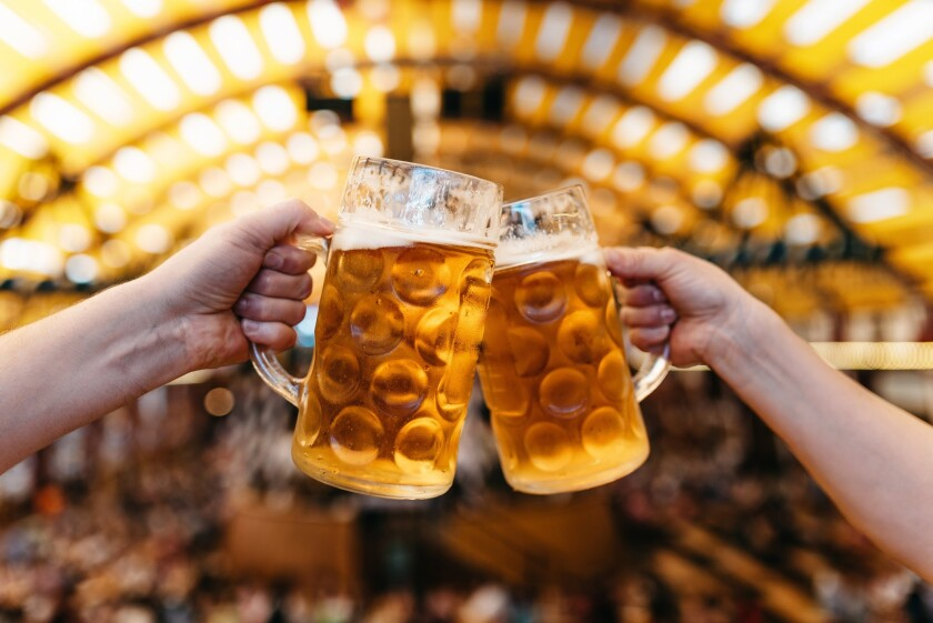 A photo of two hands clinking beer glasses