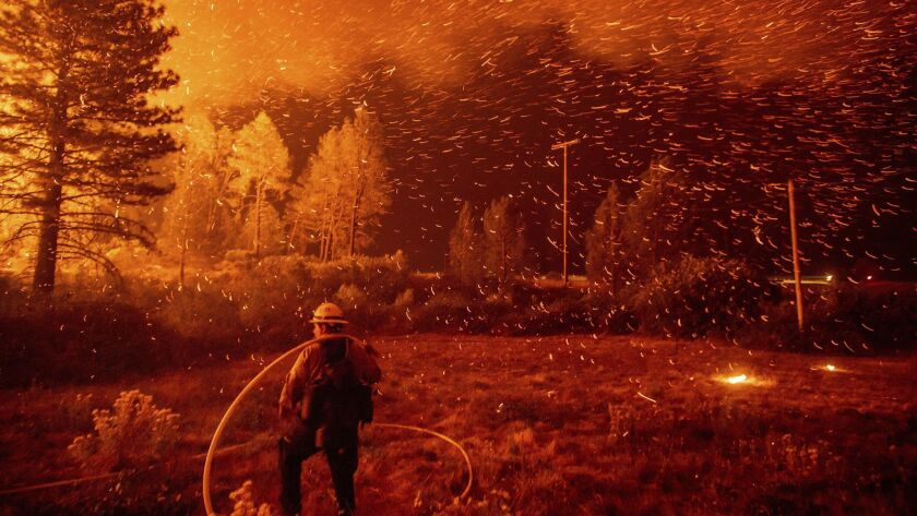 Embers fly above a firefighter as he works to control a backfire while the Delta fire burns in the Shasta-Trinity National Forest on Sept. 6.