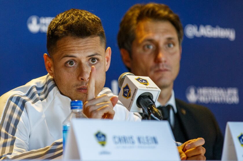 Galaxy star Javier 'Chicharito' Hernández speaks at his introductory news conference in front of Galaxy coach Guillermo Barros Schelotto.