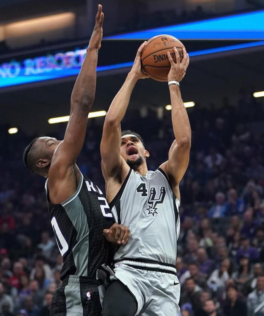 El jugador de los Sacramento Kings Derrick White (d) entra a canasta ante Harry Giles, de los San Antonio Spurs, durante un partido. EFE/Archivo