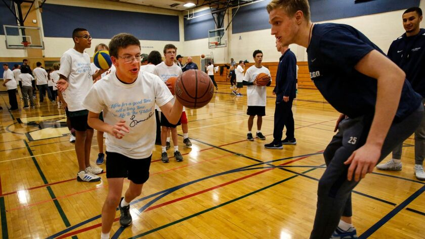 Tristan Waldner, 13, a member of the Poway Youth Basketball League's Challenged Division, tries to dribble past USD men's basketball player Yauhen Massalski.