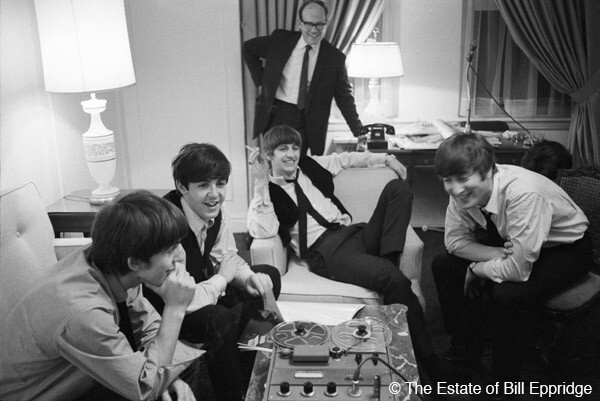 The Beatles gather 'round a reel-to-reel tape recorder at the Plaza Hotel in New York on Feb 7, 1964. From left: George Harrison, Paul McCartney, Ringo Starr and John Lennon. Copyright estate of Bill Eppridge.