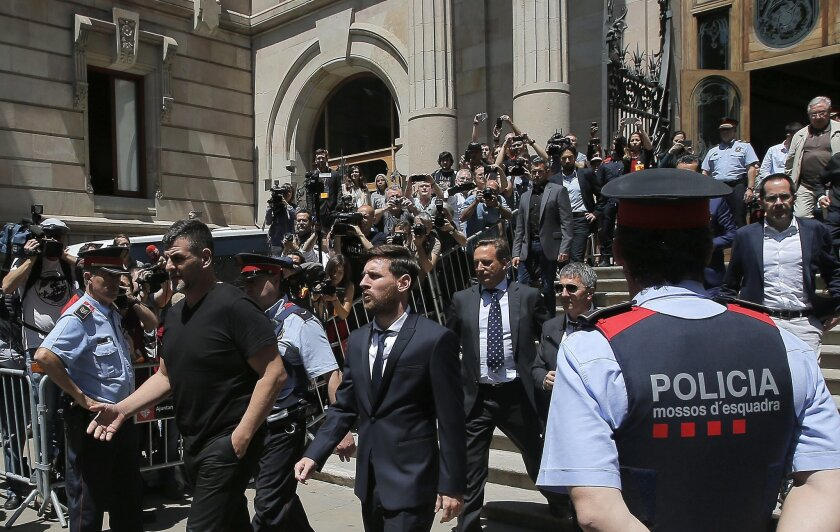 FILE - In this June 2, 2016 file photo, Barcelona soccer player Lionel Messi, center, leaves a court in Barcelona, Spain, Thursday, June 2, 2016. Barcelona has drawn widespread criticism for its campaign to support Lionel Messi after a court found the Argentine forward and his father guilty of tax