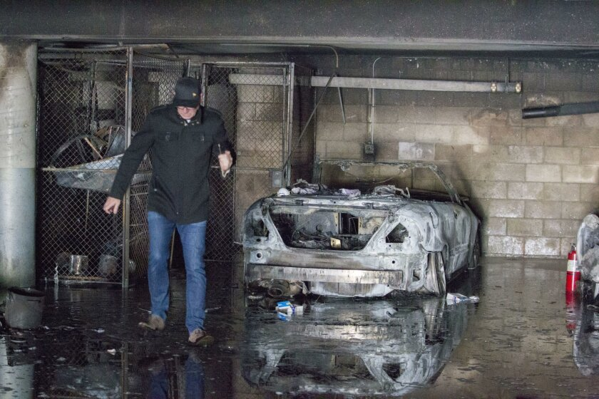 The owner of a charred Mercedes-Benz surveyed the damage after an underground garage fire at a Hillcrest apartment building Friday.