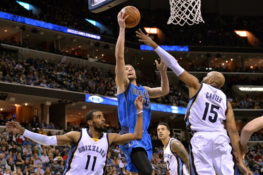Dallas Mavericks forward Chandler Parsons (25) shoots between Memphis Grizzlies guards Mike Conley (11) and Vince Carter (15) in the first half of an NBA basketball game Saturday, Feb. 6, 2016, in Memphis, Tenn. (AP Photo/Brandon Dill)