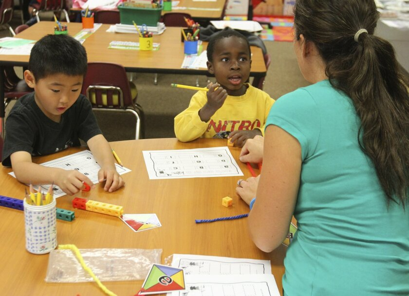 Sabrina Dadalt, a parent volunteer in Alicia Jaime's transitional kindergarten class at Cole Canyon Elementary School in Murrieta, helps Alex Fugiwara and Colt Woods work on a math-themed game.