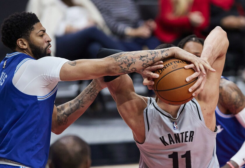 Lakers forward Anthony Davis tries to steal the ball from Trail Blazers center Enes Kanter.