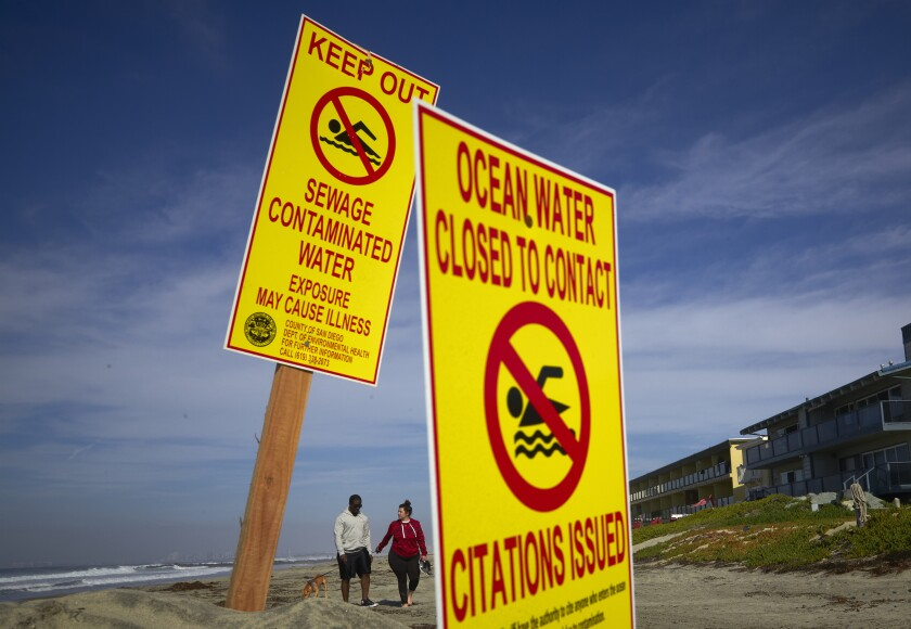 FILE - In a Wednesday, Dec. 12, 2018 file photo, a couple walk along the beach as signs warn of contaminated water at Imperial Beach, Calif. The San Diego region will get $300 million in federal funding for a new U.S. facility to capture sewage spills from Mexico before they foul shorelines north of the border. The Los Angeles Times reported Sunday, Feb. 2, 2020, the money will be allocated thanks to language included in the overhaul of the North American Free Trade Agreement signed by President Trump on Jan. 29. (AP Photo/Gregory Bull, File)