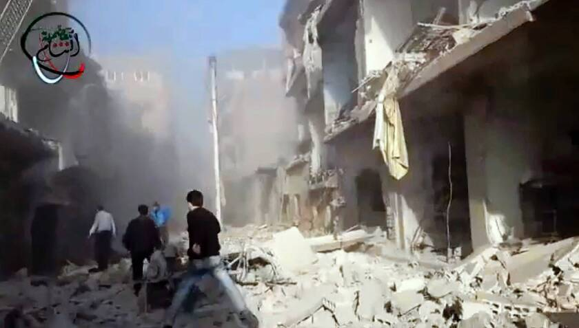 In an image from video provided by the opposition Shaam News Network, Syrian men are seen rushing to the aid of people injured in Moadamiyeh, a suburb of Damascus, the capital.