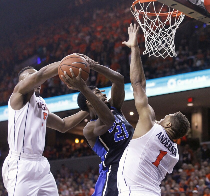 Virginia forward Darion Atkins, left, fouls Duke forward Amile Jefferson (21) during the first half of a game Jan. 31.