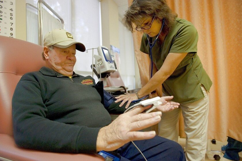 Roger Berg, 69, had his blood pressure checked by Deborah Spalding, a nurse with St. Paul's Program of All-Inclusive Care for the Elderly, which provides seniors with enough help to live at home.
