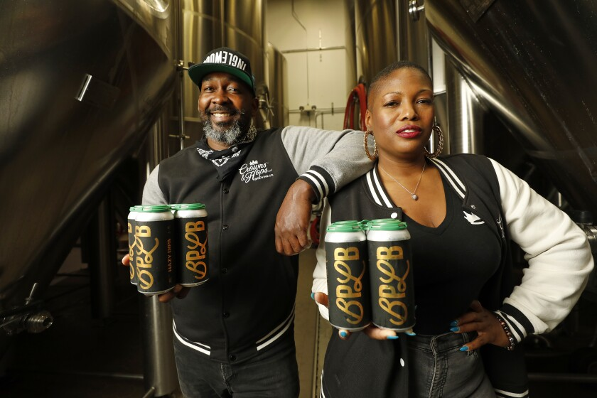 Teo Hunter and Beny Ashburn hold up cans of their BPLB beer.