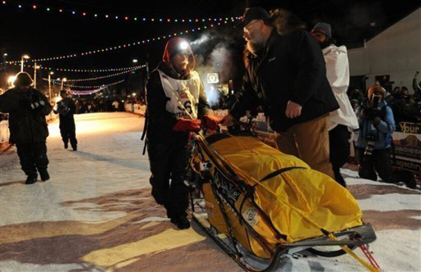 Mitch Seavey became the oldest winner, a two-time Iditarod champion, when he drove his dog team under the burled arch in Nome on Tuesday evening, March 12, 2013. Race marshal Mark Nordman is at right.  (AP Photo/The Anchorage Daily News, Bill Roth)  LOCAL TV OUT (KTUU-TV, KTVA-TV) LOCAL PRINT OUT (